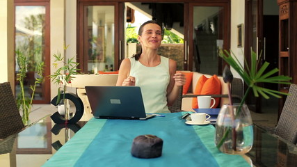 Businesswoman reading great news on laptop computer by table
