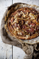 whole rustic figs tart with almond slices on vintage set