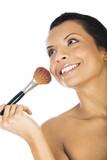 Beautiful woman applying blush with makeup brush on white