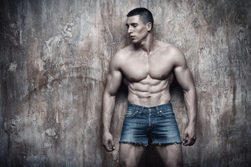 Handsome sexy muscular man on wall background