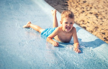 Child on water slide at aquapark, summer holiday