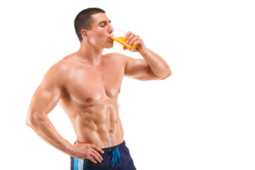Handsome muscular man drinking juice, isolated on white