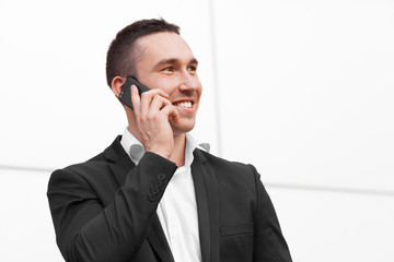 Young happy man talking on mobile phone