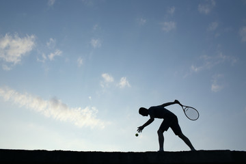 Silhouette of man playing tennis