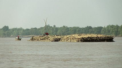 Bamboo rafts on the mekong river towed by a small boat (2)