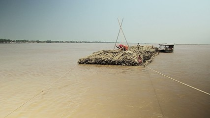 Bamboo rafts on the mekong river towed by a small boat (4)
