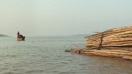 Bamboo rafts on the mekong river towed by a small boat (3)