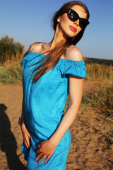 beautiful young woman in blue dress and sunglasses
