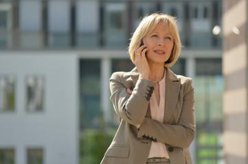 Reifere Geschäftsfrau telefoniert mit Smartphone