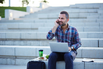 Modern businessman working and talking on the phone outdoors