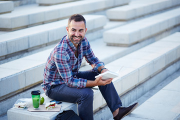 Modern businessman reading outdoors