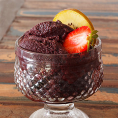 Acai pulp in glass with strawberry and kiwi