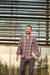 Modern businessman standing outside office