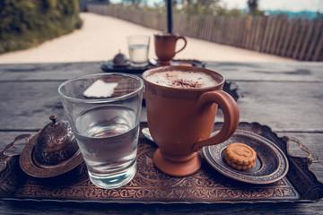 Чашка кофе, стакан воды и печенье на деревянном столе.