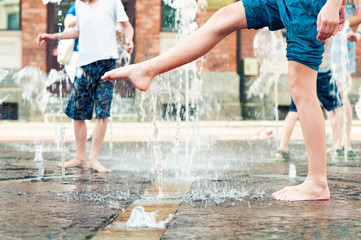Summertime enjoyment. Kids legs in fountain