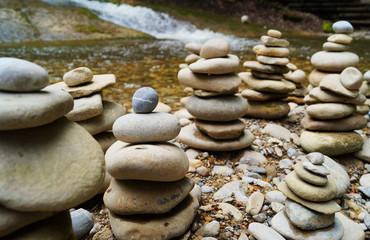 Flache Steine gestapelt zu Türmen an einem Bach