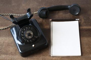 Altes Telefon mit Schreibblock und Bleistift