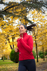 Cheerful woman running in autumn park