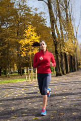 Female athlete running in autumn park