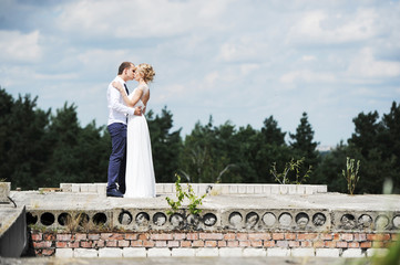 the groom and the bride kiss on ruins