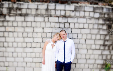 The groom and the bride against a brick wall