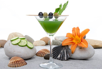 Green vegetables cocktail in a environment of sand and pebble st