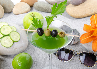 Healthy green vegetables cocktail on a beach environment