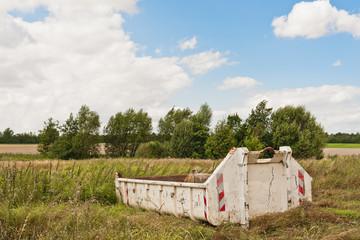 Ein Bauschuttcontainer steht auf einer Wiese