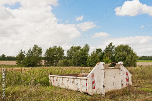 canvas print picture Ein Bauschuttcontainer steht auf einer Wiese