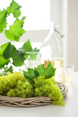 Fresh white grapes in basket and wine on the table