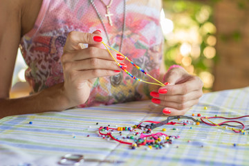 Woman making beaded braclet with her hands