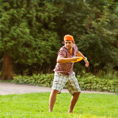 man playing in the park with a plate frisbee