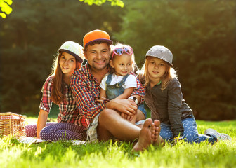 Father and his three daughters in a park on a picnic