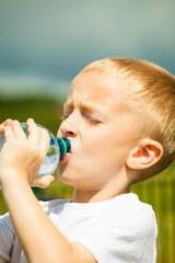 Little boy drink water from bottle, outdoor
