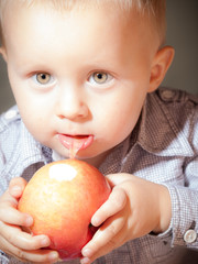 Cute baby boy eating red apple fruit