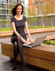 young woman working on laptop computer outdoors.