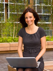 Young woman working outdoors on her laptop