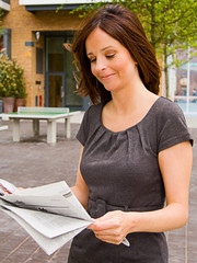 a young woman reading the newspaper.