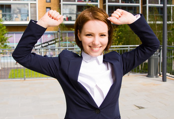 a young business woman celebrating an acheivement.