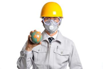 地球儀を持っているヘルメットと防塵マスクを付けた男性