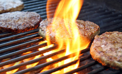 Burgers Cooking Over Flames On The Grill