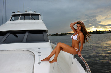 Seductive model in white bikini posing on the luxury yacht.