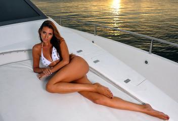 Beautiful woman relaxing on yacht deck and wearing bikini.