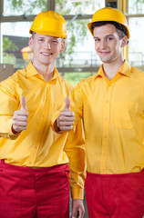 Warehouse workers showing thumbs up sign