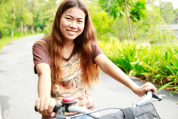 close up young happy asia girl riding bicycle relax in a park