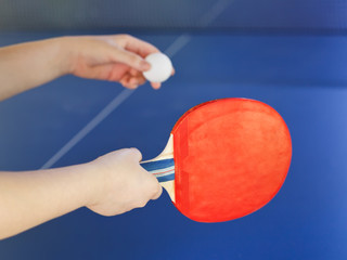 girl plays in table tennis with red racket