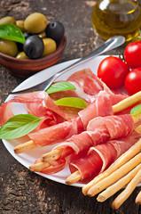 Grissini bread sticks with ham, olives, basil on table