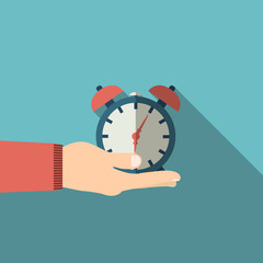 Hand holding alarm clock in flat design on background
