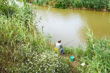 fisherman is fishing on riverbank