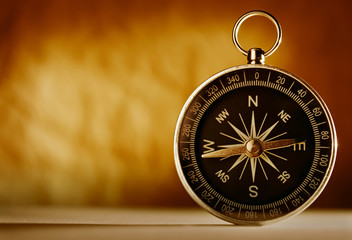 Magnetic compass against a vintage background